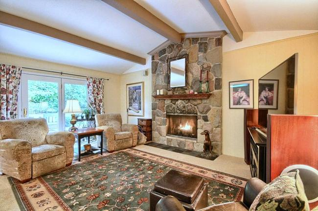 family room with vaulted ceilings and a stone fireplace